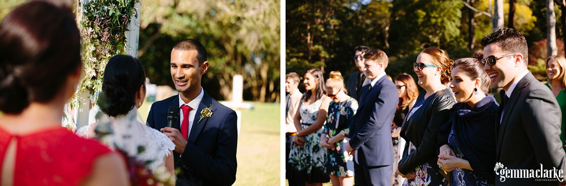 Wedding guests smile and look on as the groom speaks into a microphone