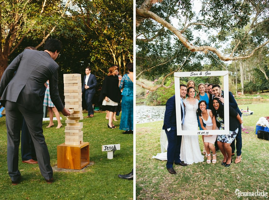A bride and some of her wedding guests post behind a large frame as some other guests play a game of giant jenga