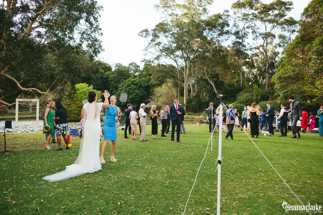 A bride high fives a guest as they play badminton