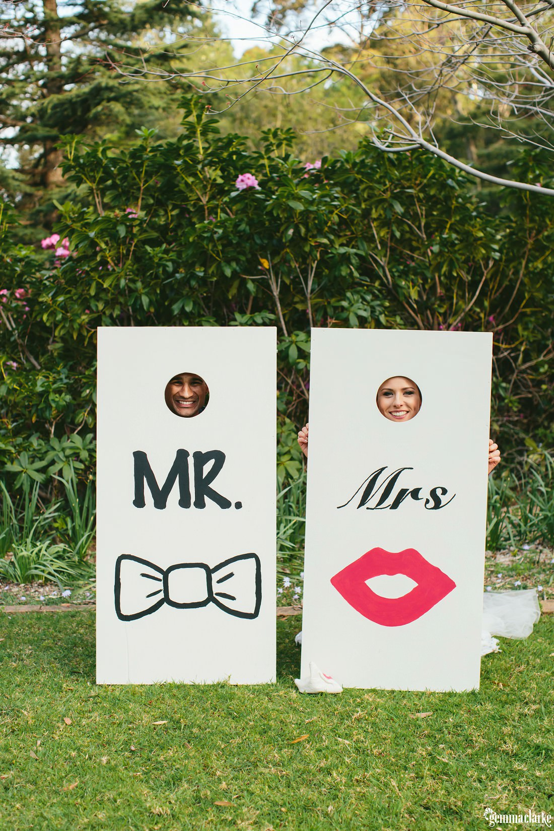 "Large ""Mr and Mrs"" boards with holes in them, the bride and groom stick their faces through and pose for a photo"
