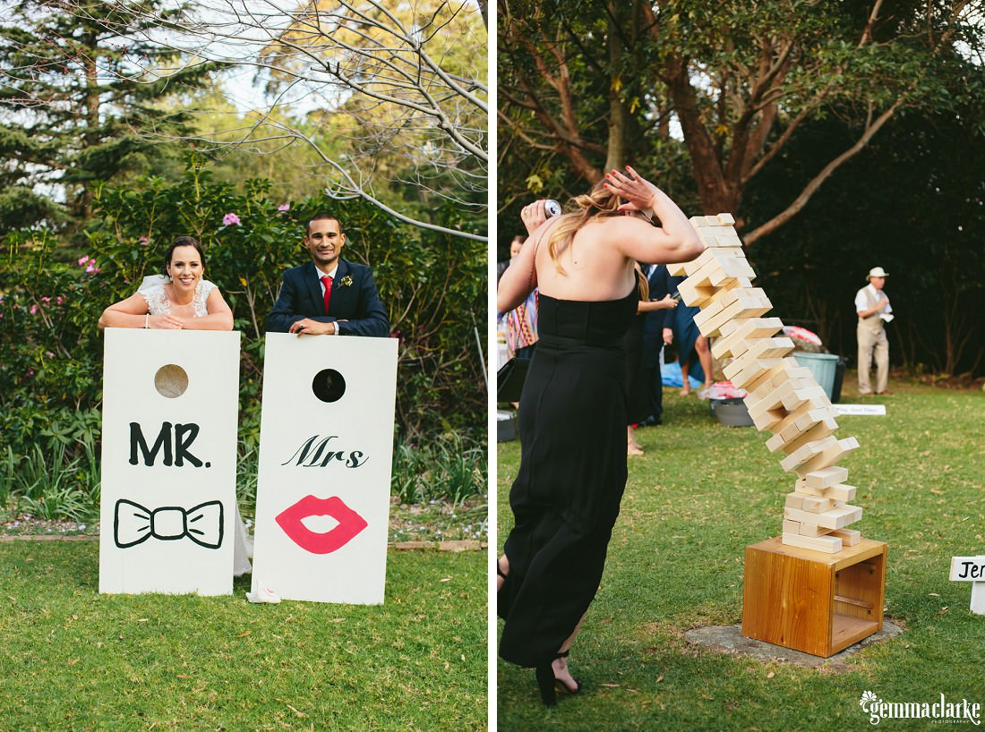 "A bride and groom leaning on large boards that say ""Mr"" and ""Mrs"" on them, and wedding guests playing giant jenga"