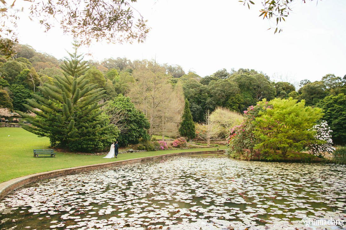 A bride and groom walking around a pond in a large garden