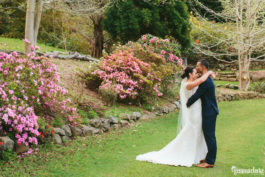 A bride and groom embrace in a garden