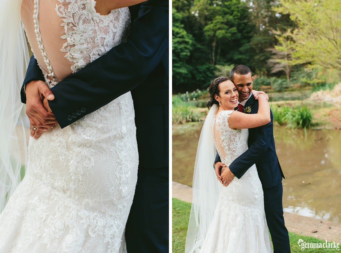 A smiling bride and groom embrace in front of a pond