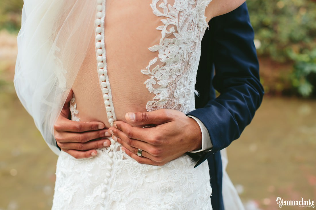 A groom's hands around his bride's waist