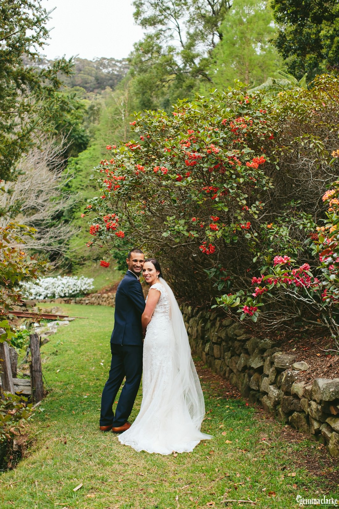 A bride and groom in a garden smiling back over their shoulders