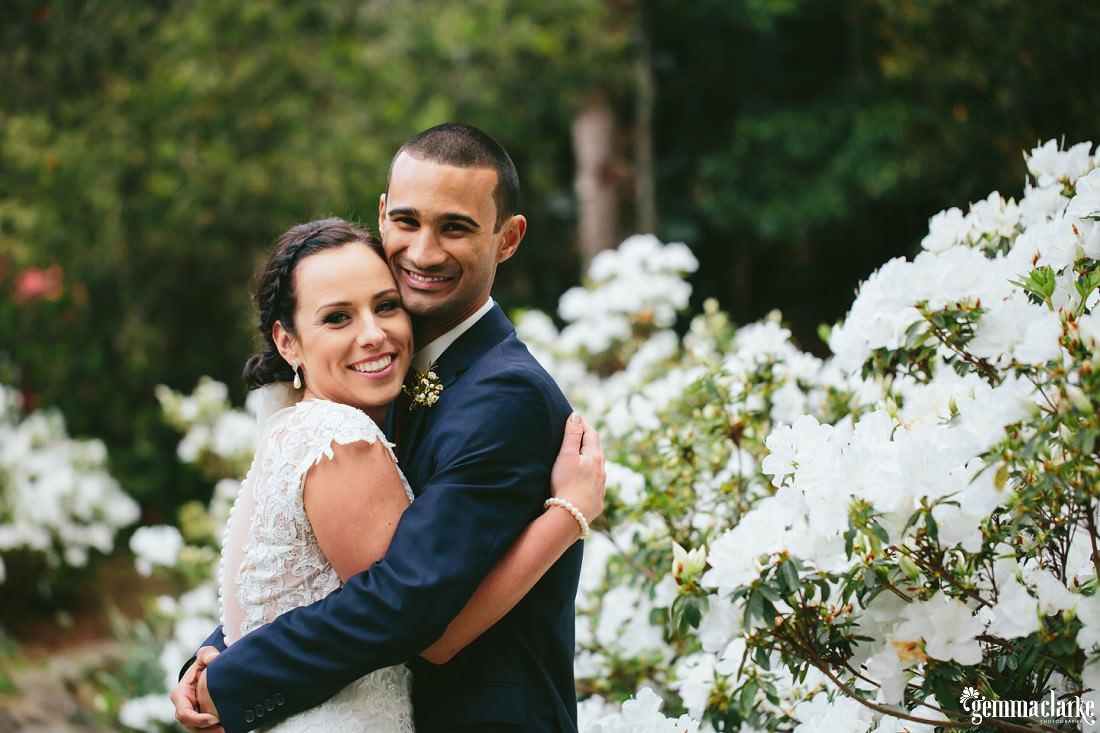 A smiling bride and groom embracing in front of a plant covered with white flowers