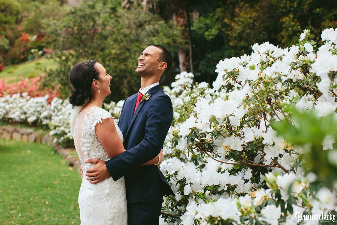 A bride and groom embracing and laughing in front of some white flowers