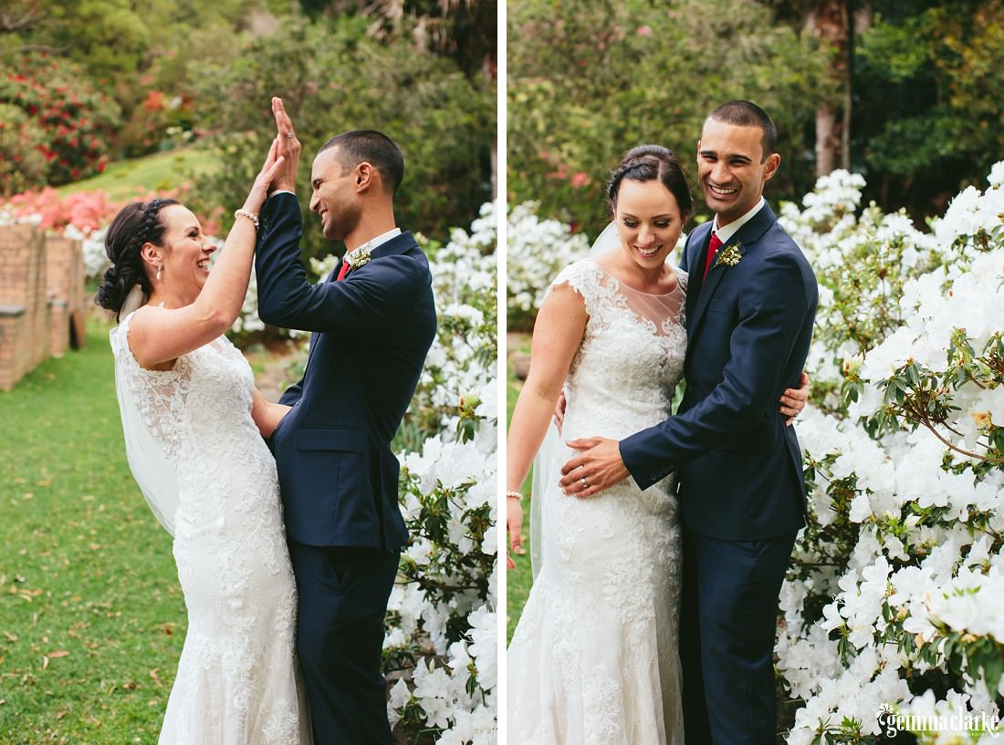 A bride and groom embracing and high fiving in front of some white flowers