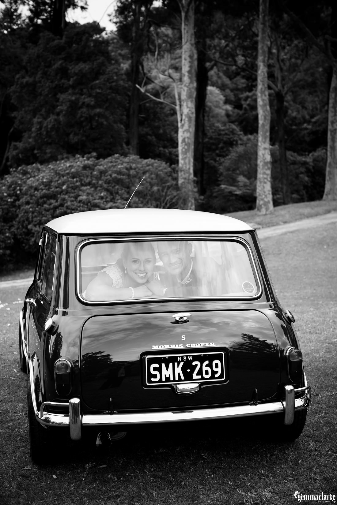 A smiling bride and groom look out from the back of a classic Mini