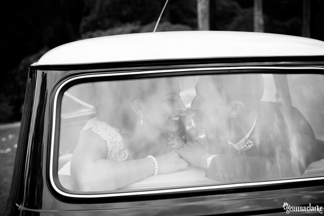 A bride and groom smiling at each other in the back of a classic Mini