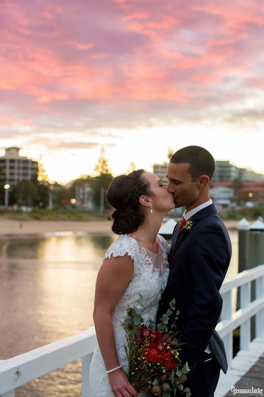 A bride and groom kiss while standing on a wharf as the sun sets in the background