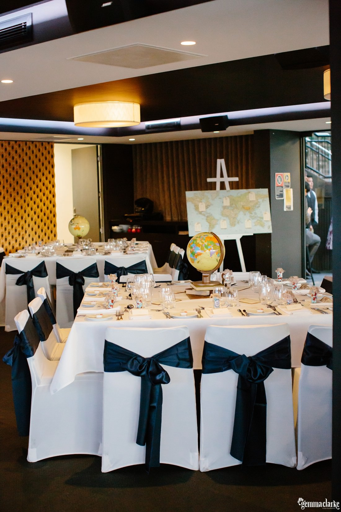 A wedding reception setup with white tables and chairs and decorative maps and world globes