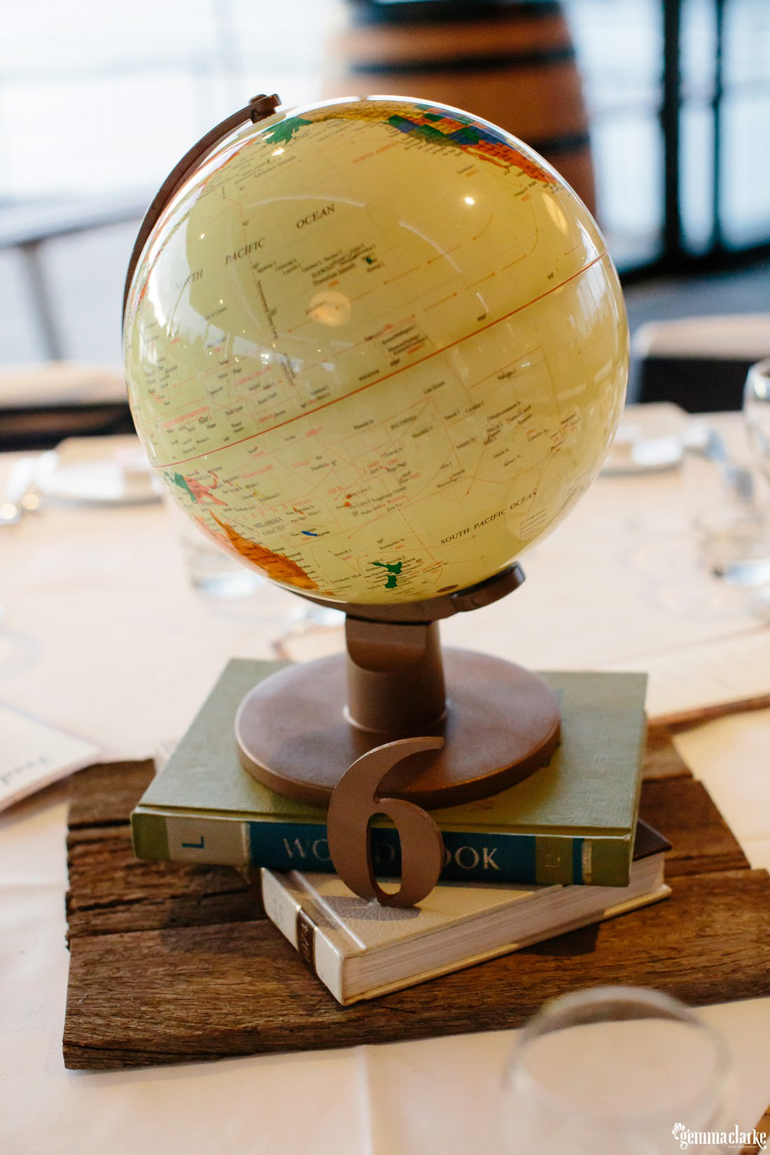 A table number with decorative books and world globe