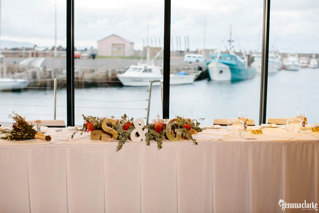 "A bridal table with ""S & G"" surrounded by flowers, and boats on the water visible through the window in the background"
