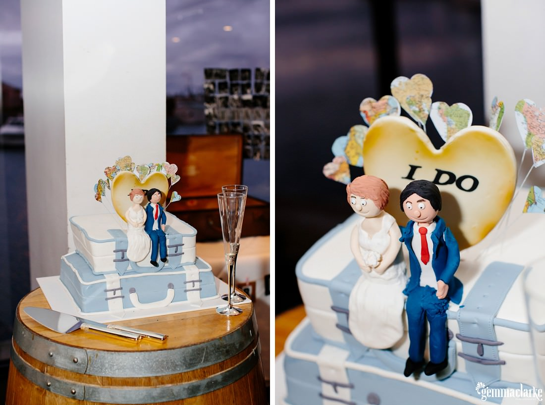 "A wedding cake in the shape of two suitcases with a bride and groom figure sitting on top with a love heart shaped sign that says ""I Do"""