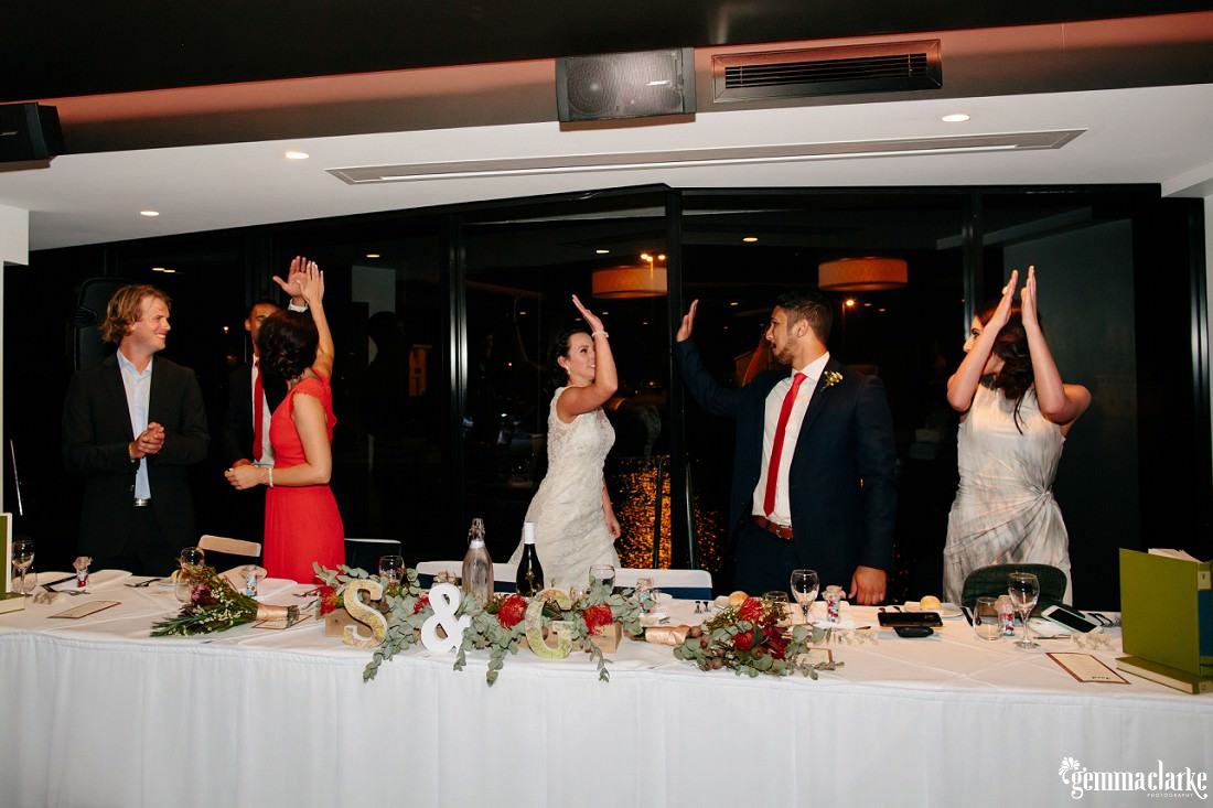 Bridal party giving each other high fives at the bridal table