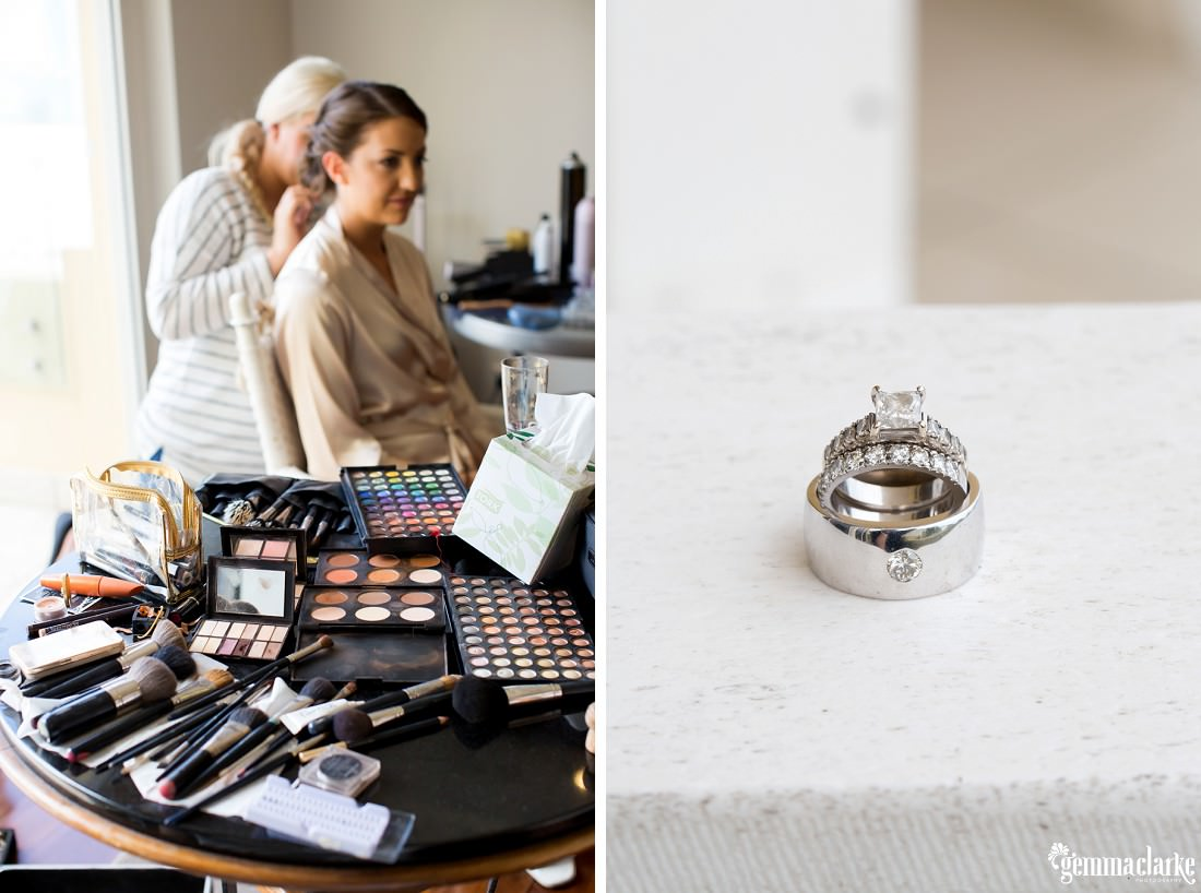 A bridesmaid having her hair done and a closeup of three white gold rings on a marble counter