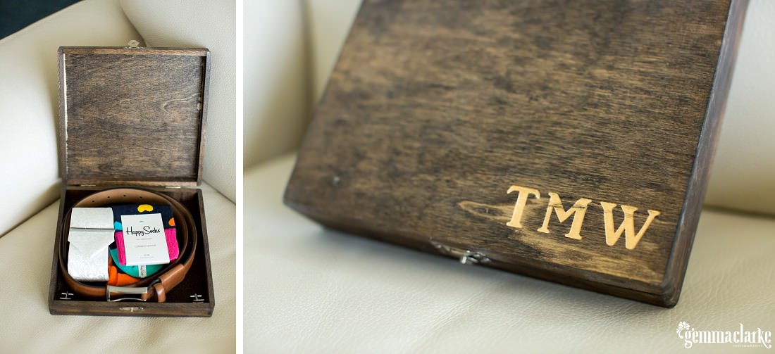 A wooden box labelled with the groom's initials, with men's accessories inside including a belt and socks