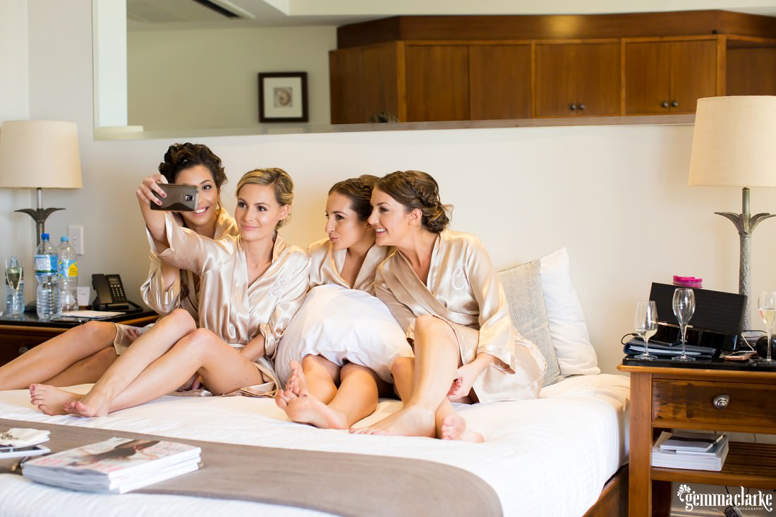 Four bridesmaids wearing robes and sitting on a bed smile as one takes a selfie with her phone