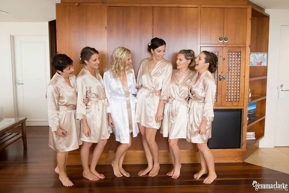 A bride and her four bridesmaids and her mother wearing robes, standing and laughing with each other