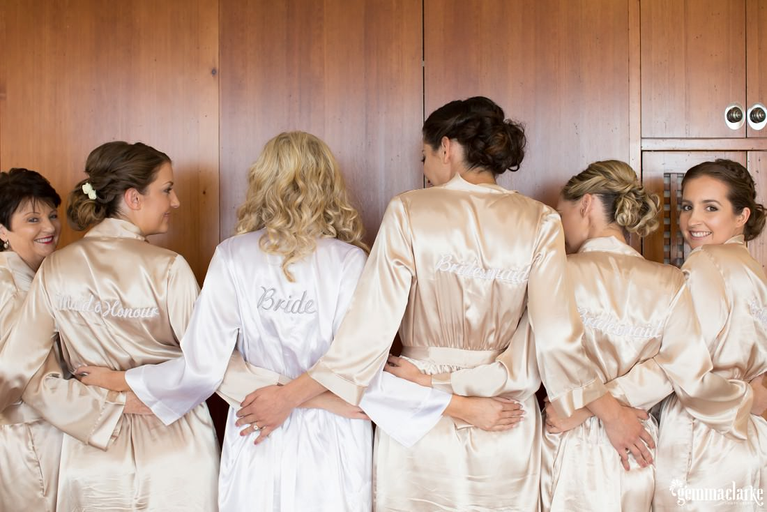A bride and her four bridesmaids and her mother standing with the backs of their robes showing their labels (bride, maid of honour, bridesmaid, etc)