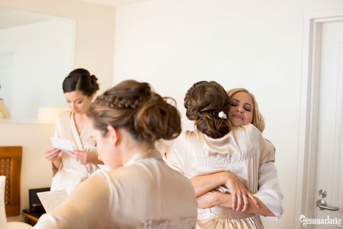 A bride getting a hug from her maid of honour