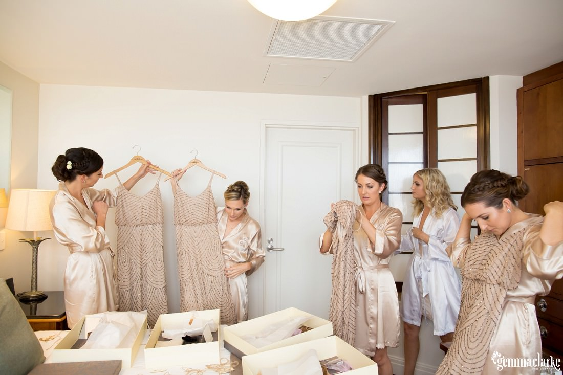 A bride looks on as her bridesmaids inspect their dresses