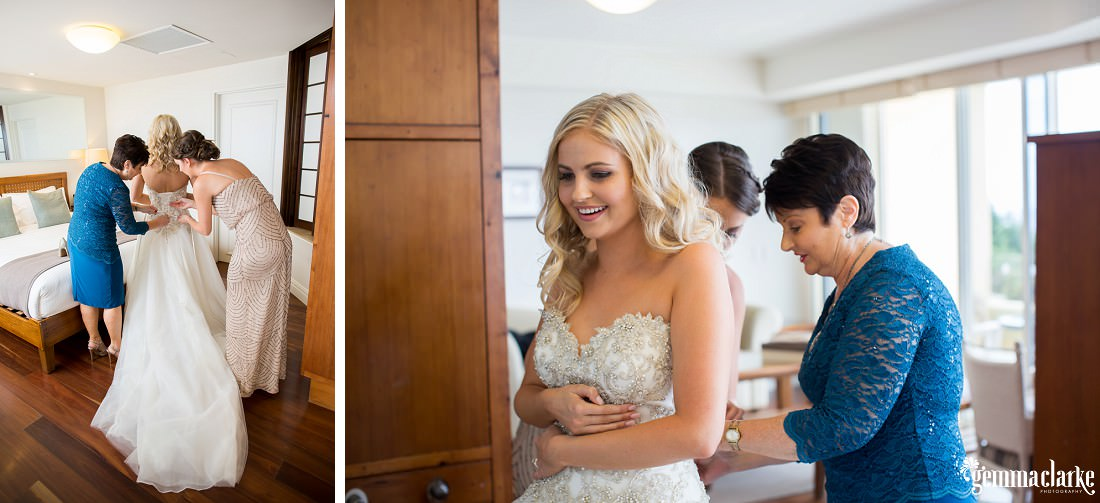A bride having the back of her dress done up by her mother and maid of honour