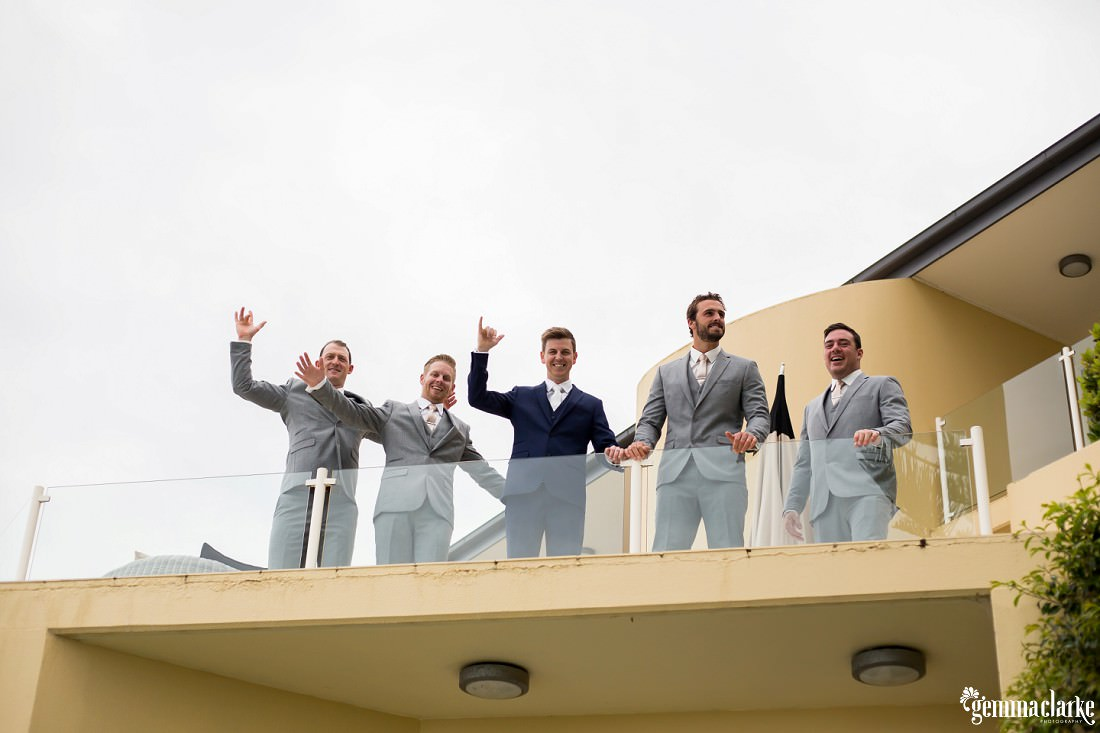 A groom and his groomsmen waving from a balcony