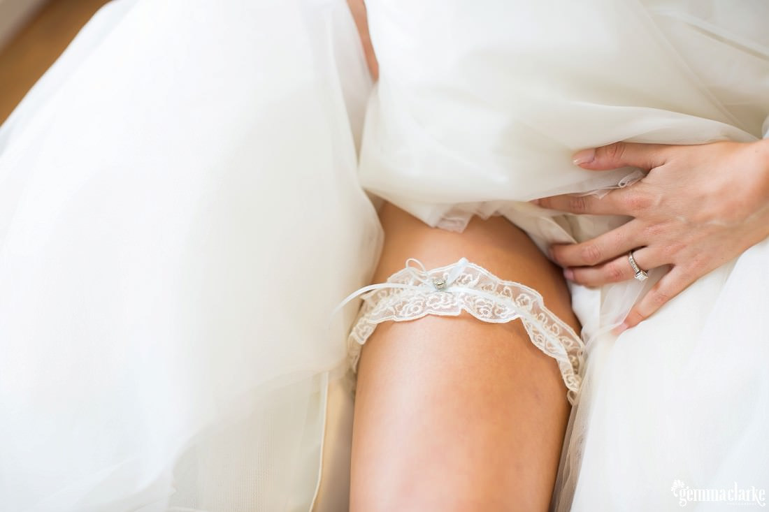 A closeup of a bride's garter with a blue bow