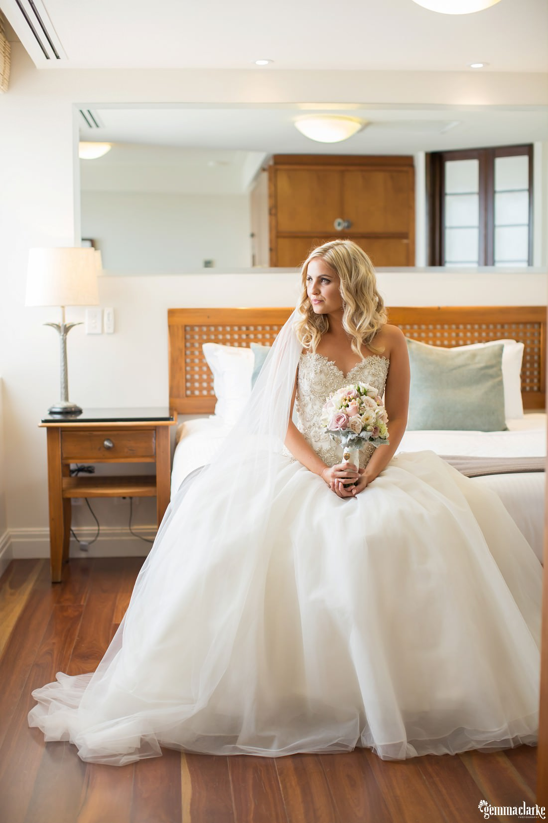 A bride in a white gown sitting on the end of a bed holding her lightly coloured floral bouquet