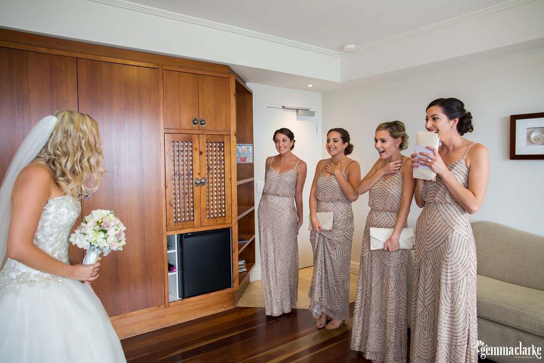 Bridesmaids react seeing the bride in her dress for the first time