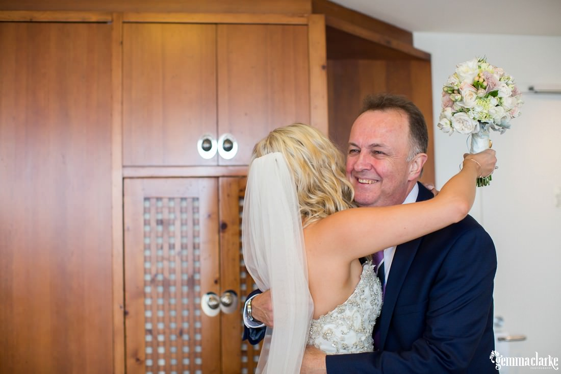 A bride hugs her smiling father
