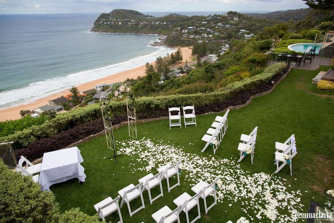 An overhead shot of an outdoor setting for a wedding reception in a green garden with a view to a beach and headland