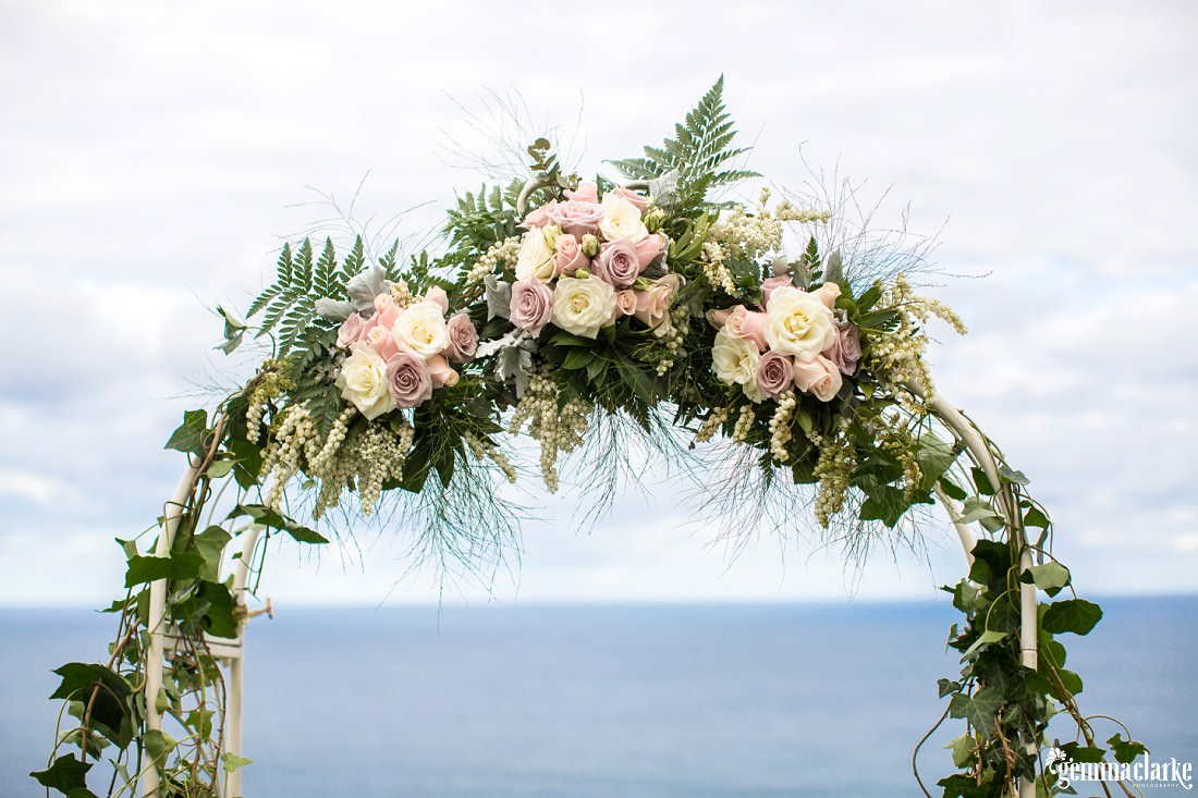 A wedding arch decorated with white and pink flowers