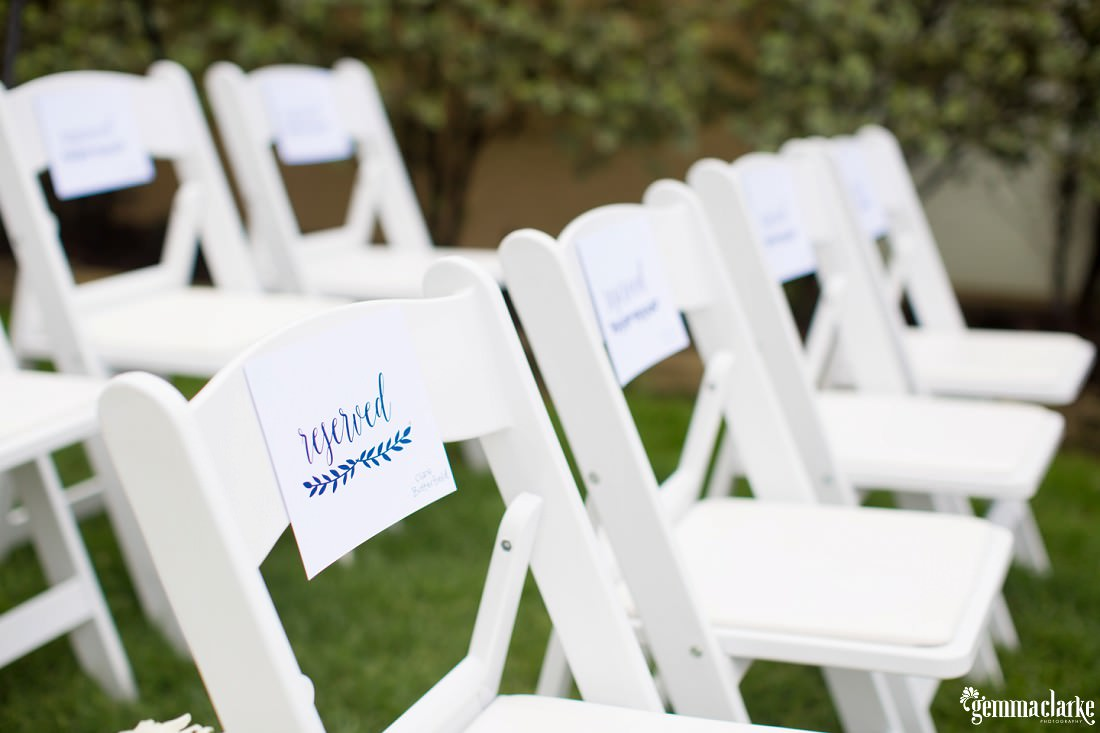 "White chairs at a wedding ceremony with ""Reserved"" signs on them"