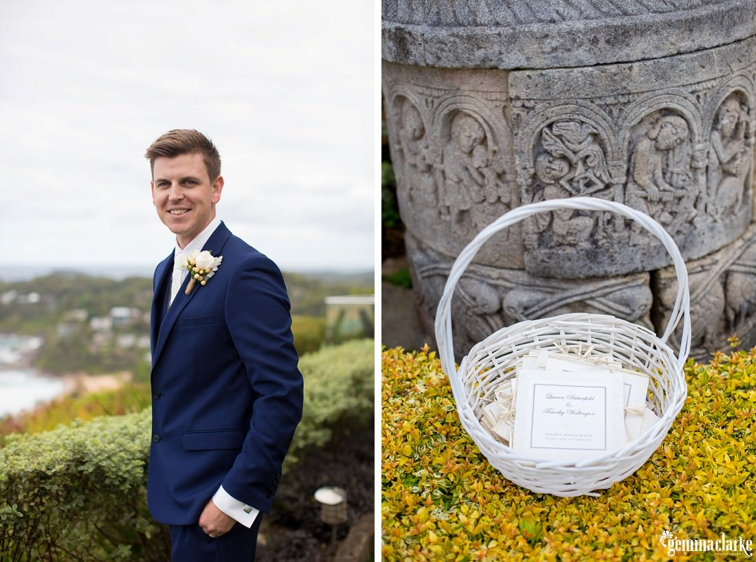 "A groom in a dark blue suit with floral buttonhole and ""Order of Service"" handouts in a white basket on flowers in front of a wishing well"