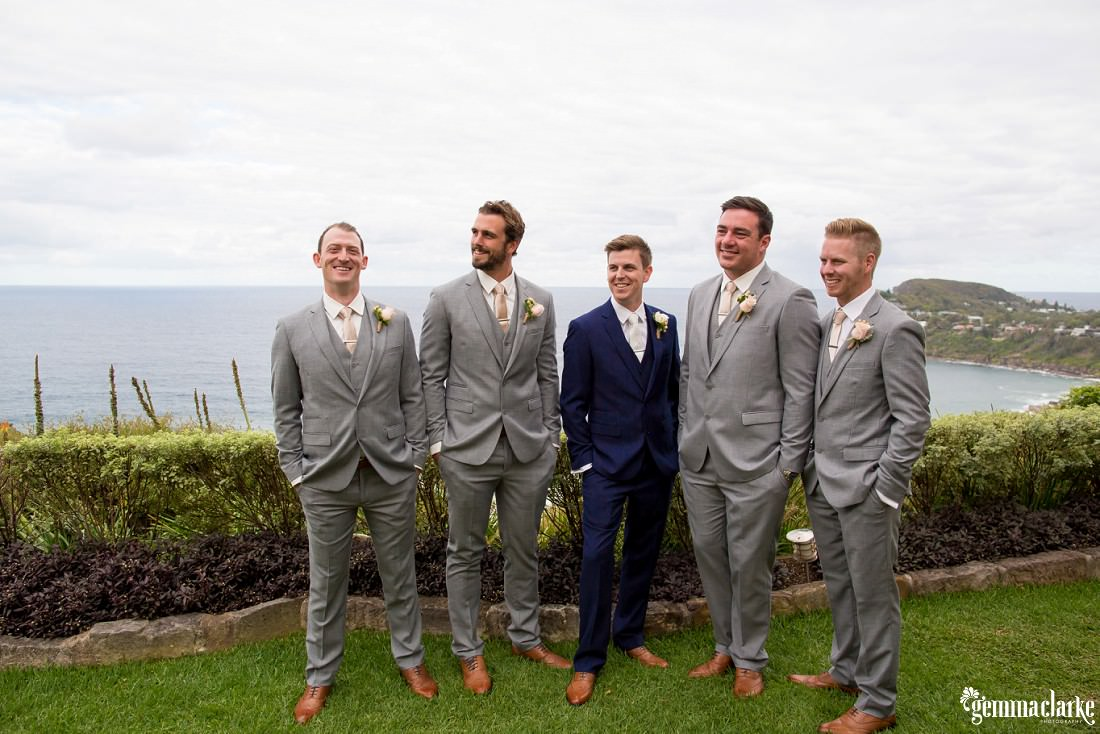 A groom and his groomsmen smiling and standing with their hands in their pockets