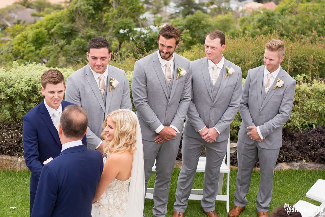 Groomsmen smile and look on as the father of the bride greets the groom and gives the bride over