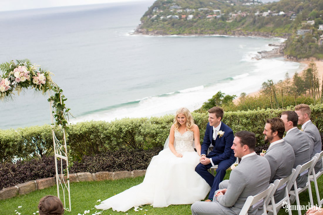 A smiling bride and groom hold hands as waves crash into the beach in the background