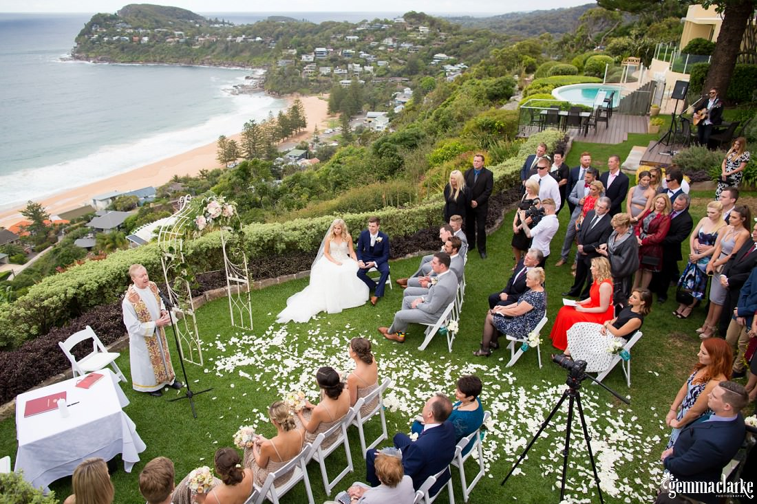 An overhead shot of a wedding ceremony in a garden with a beach and headland in the background