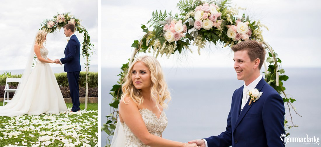 A smiling bride and groom hold hands in front of an arch decorated with flowers