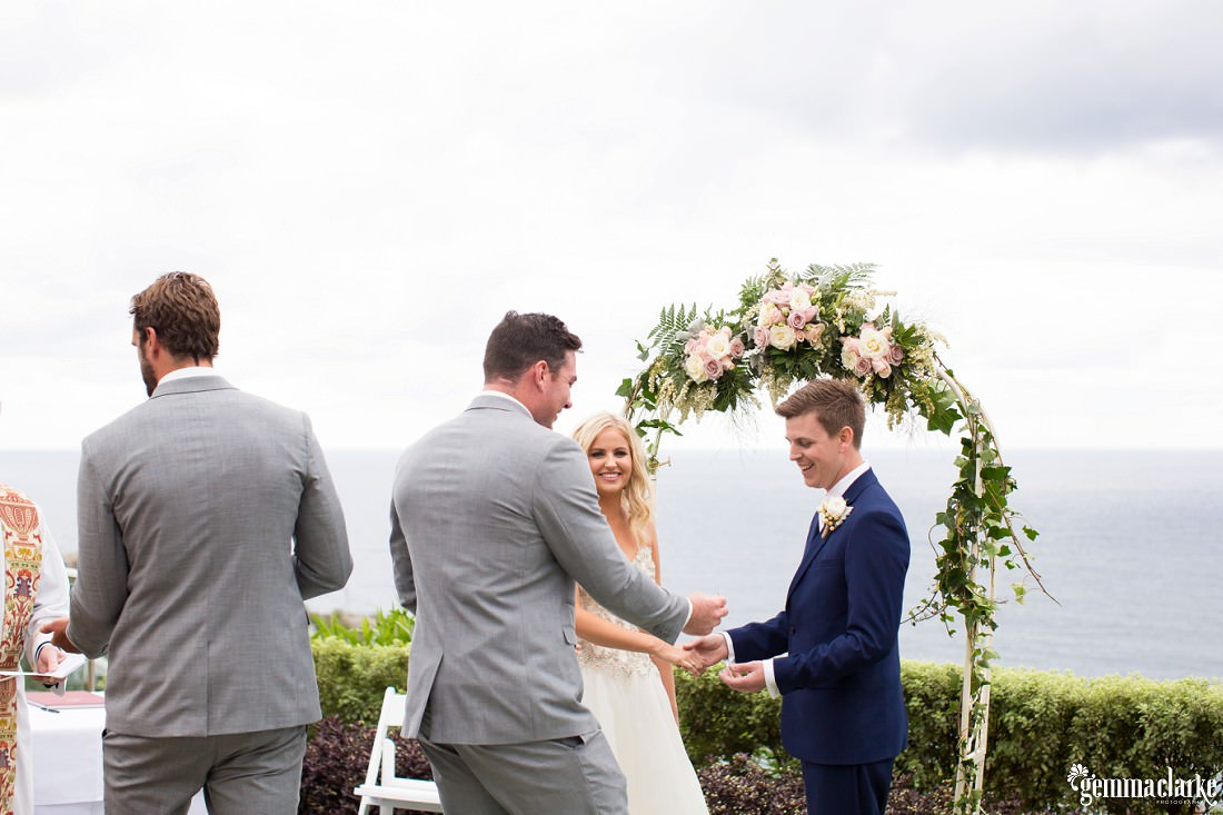 A groom is handed a ring by his best man