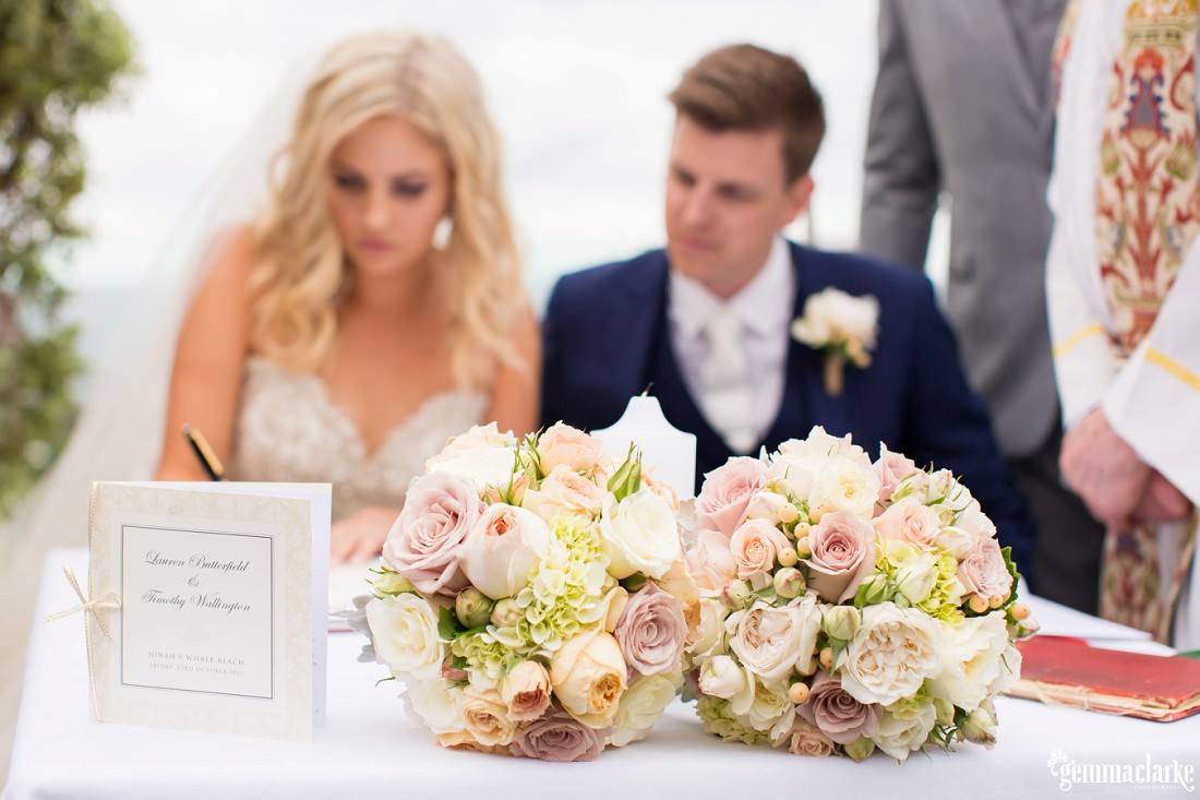 A bride and groom at the signing table with floral bouquets in the foreground