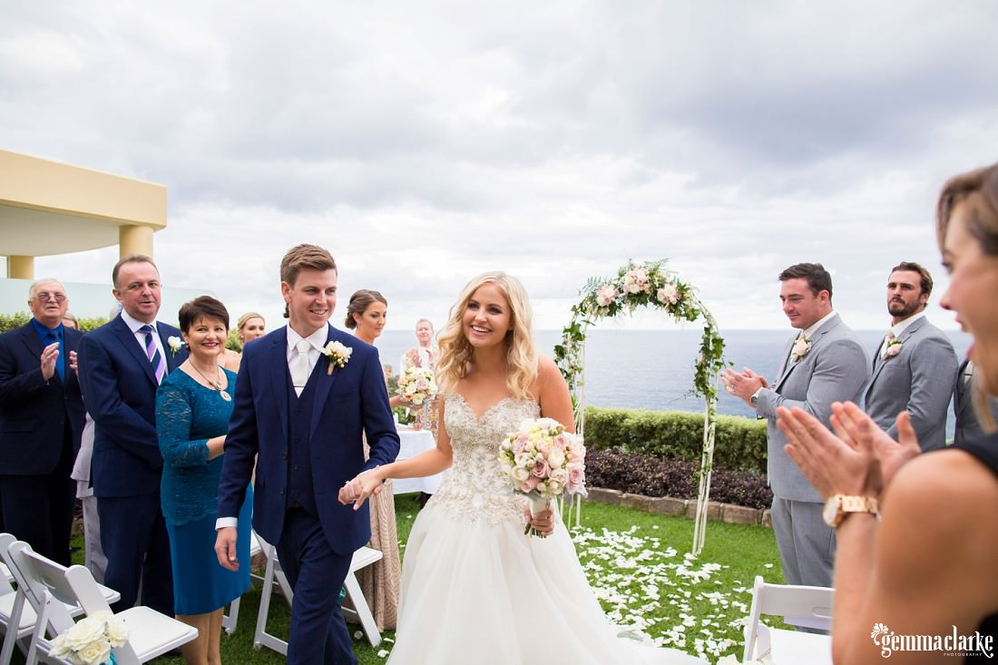 Wedding guests clap as a happy bride and groom walk back down the aisle hand in hand