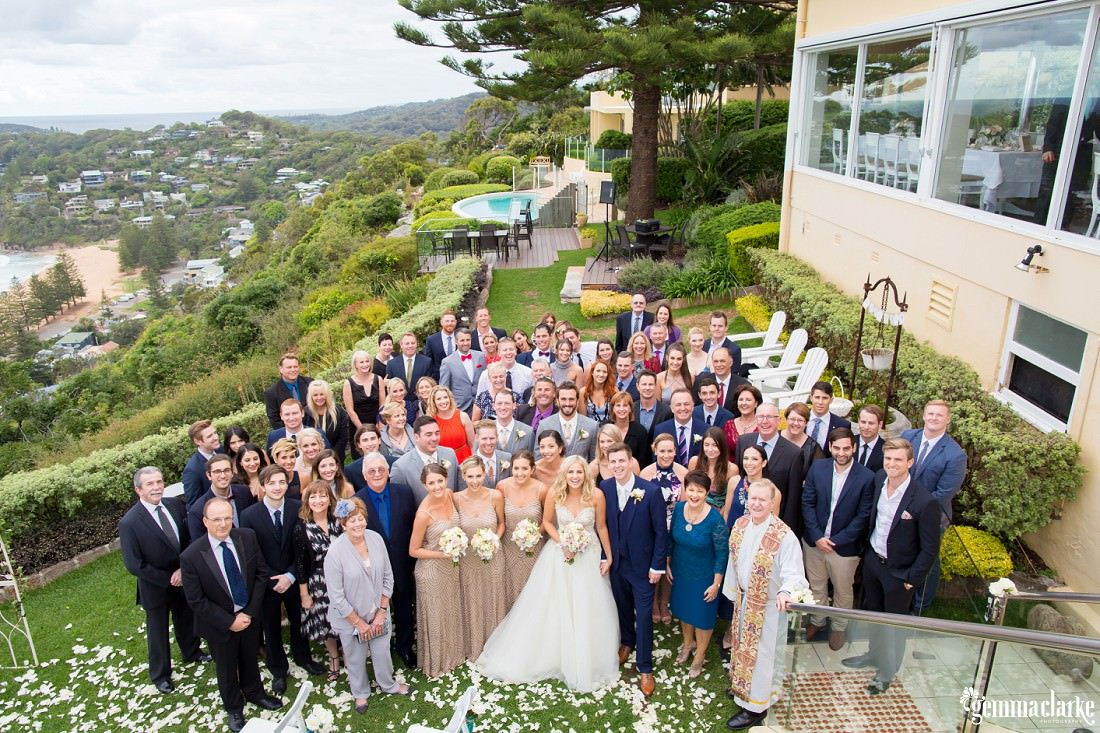 An overhead group shot of a wedding party and their guests in a garden with a beach in the background