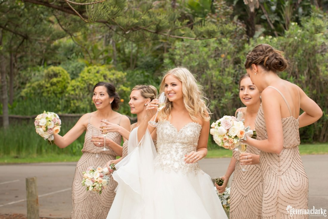 A bride and her bridesmaids smiling and talking together and sipping champagne