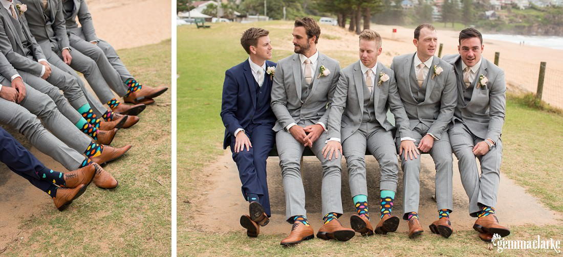 A groom and his groomsmen sitting on a bench seat near a beach with their shoes and colourful socks on display