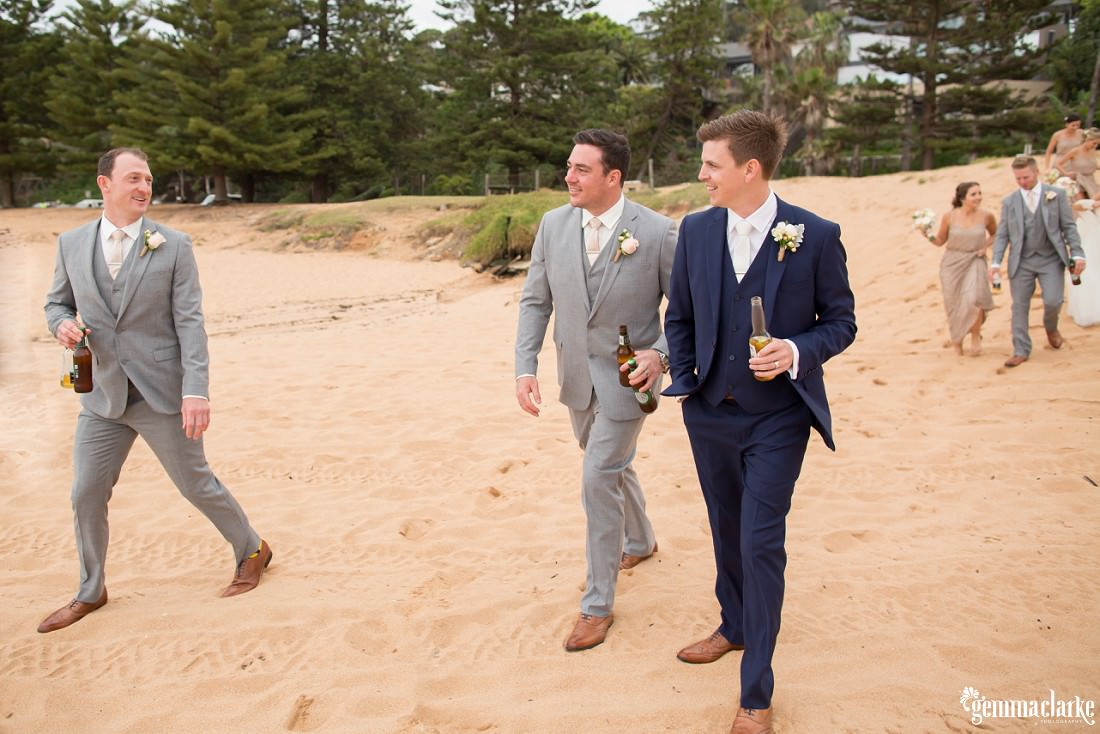 A groom and his groomsmen walking down onto a beach with beers in hand